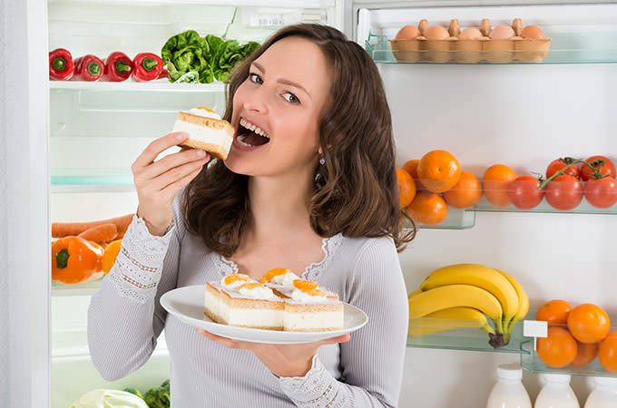 bigstock-Woman-Eating-Slice-Of-Cake-97331957