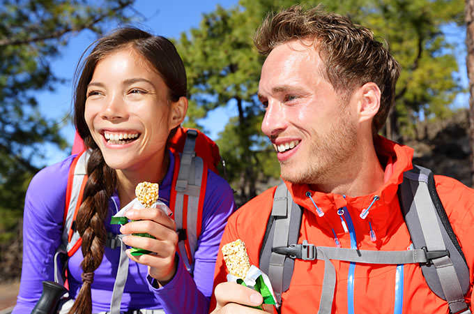 bigstock-Couple-eating-muesli-bar-hikin-74257219