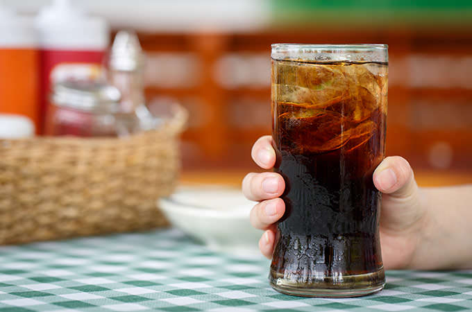 bigstock-Hand-Holding-Glass-Of-Cola-Dri-74939704