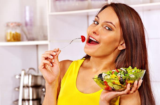 bigstock-Happy-woman-eating-salad-at-ki-70423444