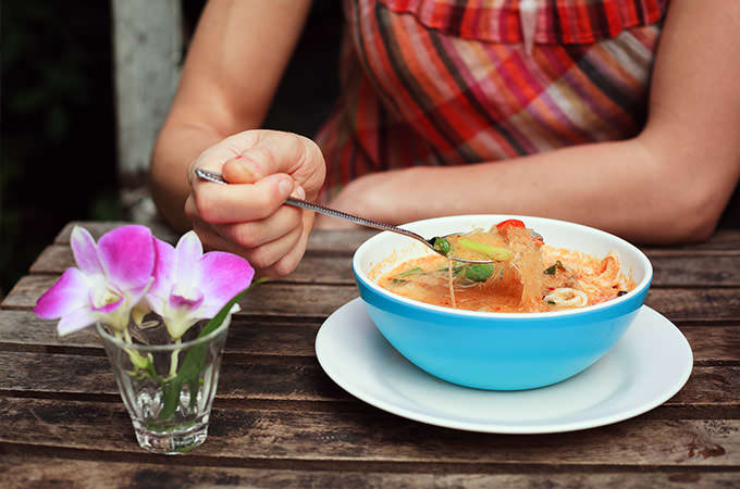 bigstock-Woman-Eating-Tom-Yum-Soup-81362696