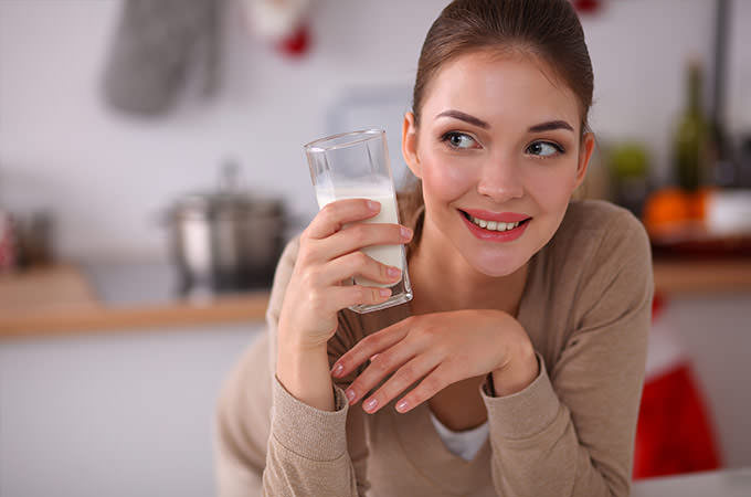 bigstock-Smiling-young-woman-drinking-m-74731066