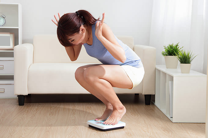 bigstock-Upset-Woman-On-Weigh-Scale-68459707