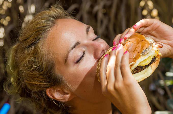 bigstock-Woman-eating-a-cheese-burger-a-96644111