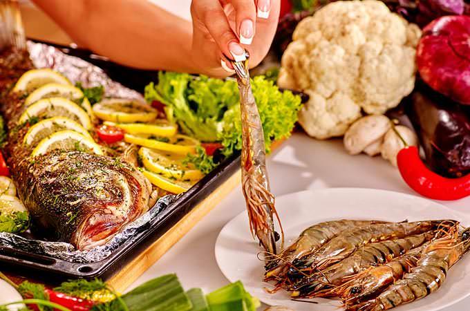 bigstock-Happy-woman-prepare-fish-at-ov-92116349