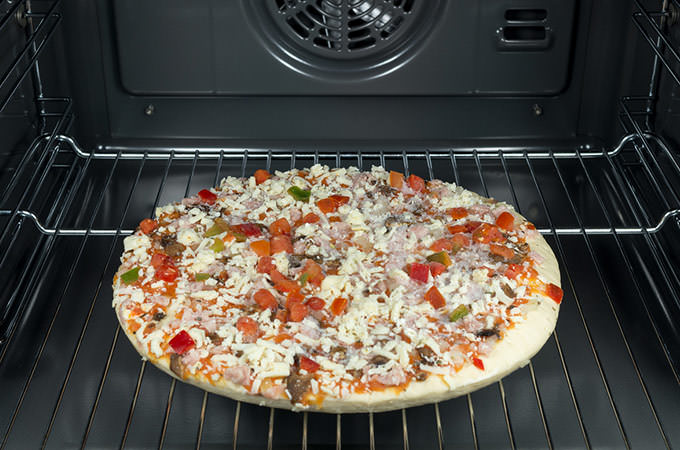 bigstock-Raw-And-Frozen-Pizza-In-The-Ov-54239315